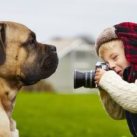 Little boy with camera is shooting his dog