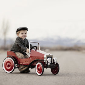 A young boy driver is out for a drive in his pedal car. Vintage black and white.