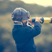 Young boy in a business suit with telescope. Small child wearing a full suit and holding a telescope. He is holding the telescope up to his eye with an aviator cap on. Business forecasting, innovation, leadership and planning concept. Shot outdoors with trees and grass in the background